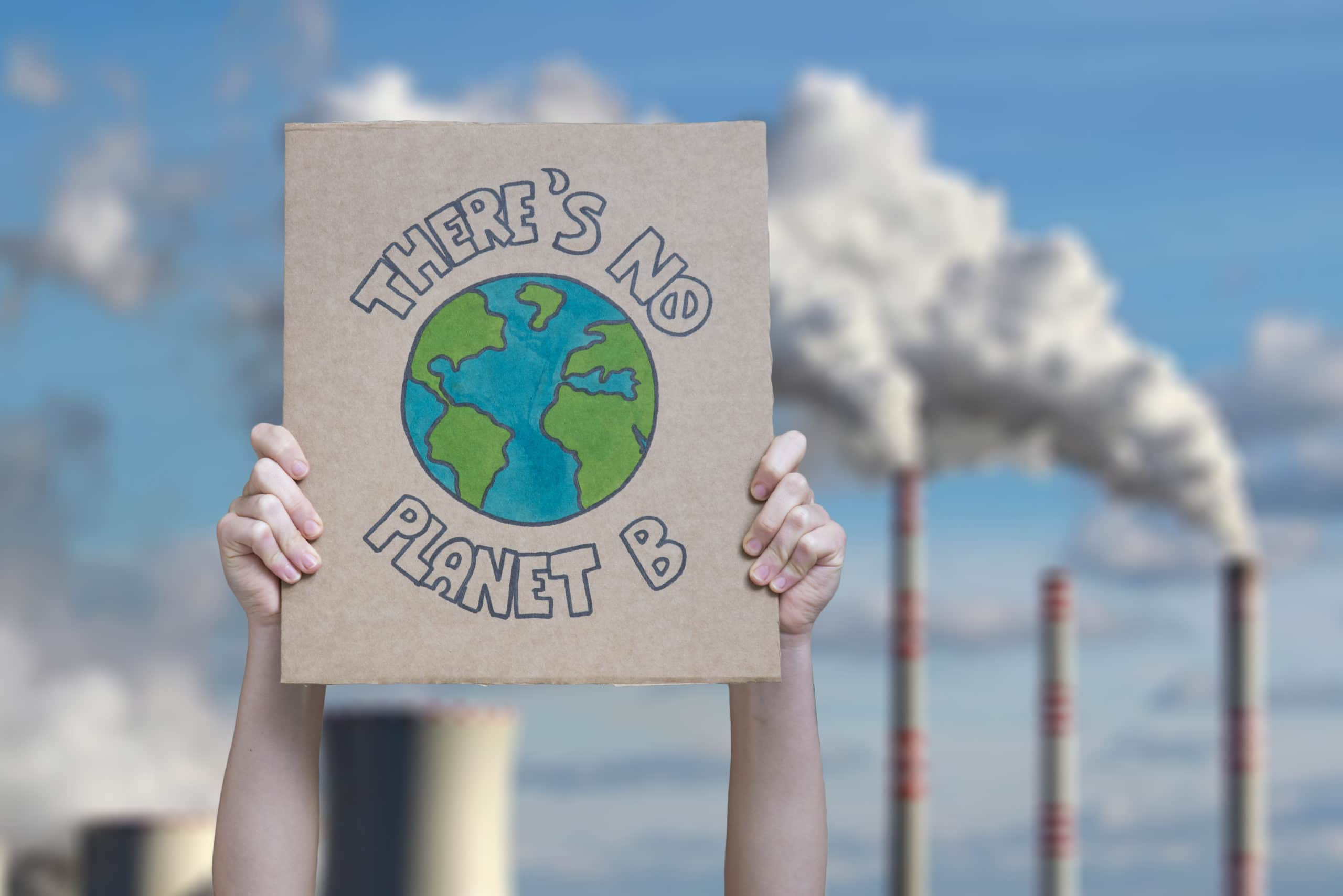 """Two hands hold a cardboard poster that reads, """"There's no Planet B"""" with industrial fossil fuel towers spewing smoke in the background."""
