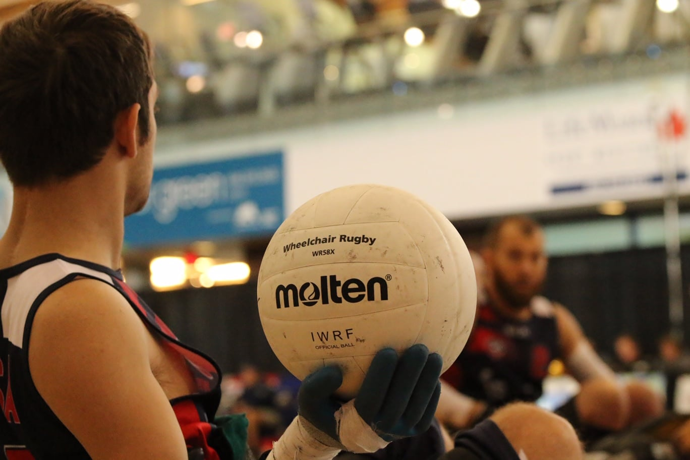 """A profile view of Butler from the chest up holding a Molten volleyball that says, """"Wheelchair Rugby"""" and """"IWRF Official Ball."""""""