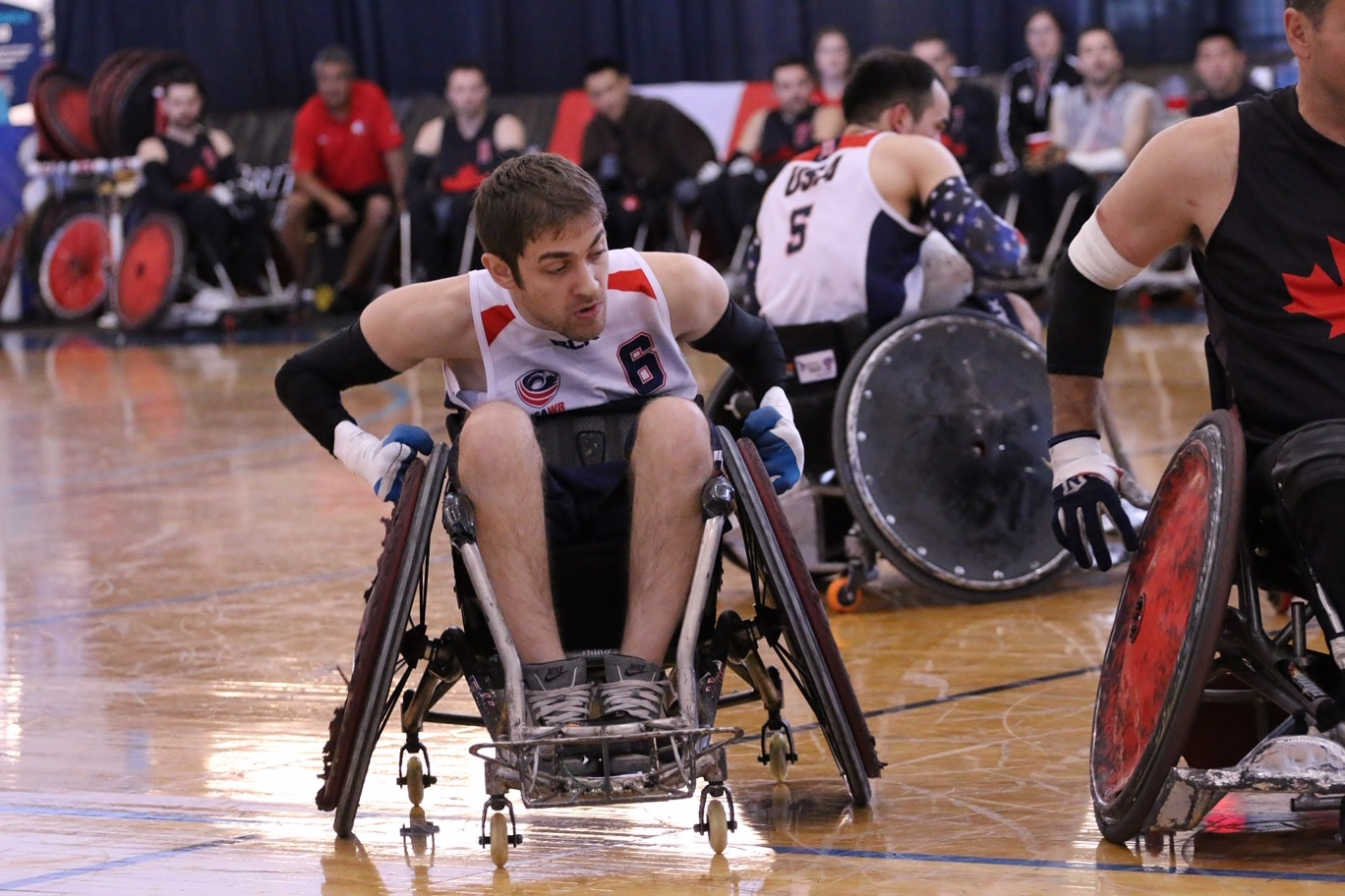 Jeff Butler wheels forward on a gym court in his rugby wheelchair. Other players are in the background.
