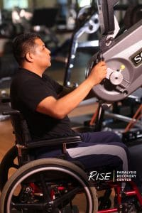 A man in his wheelchair from a profile view using a hand cycle at a gym.