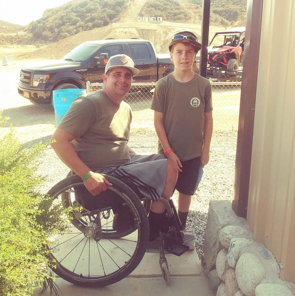 Anthony Orefice in his wheelchair with his son standing next to him.