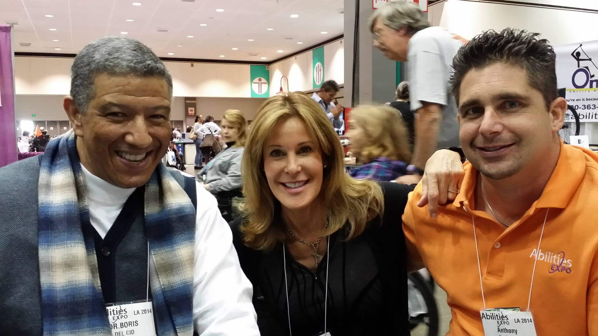 A man with Dr. Boris on a name tag next to Mayra Fornos and Anthony Orefice at Abilities Expo.