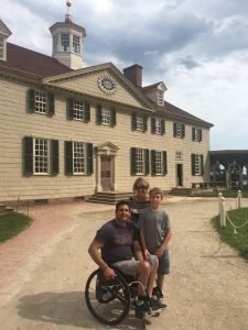 The Orefice family (Anthony, his son, and wife) on a gravel path with a large, white-brick building in the background.