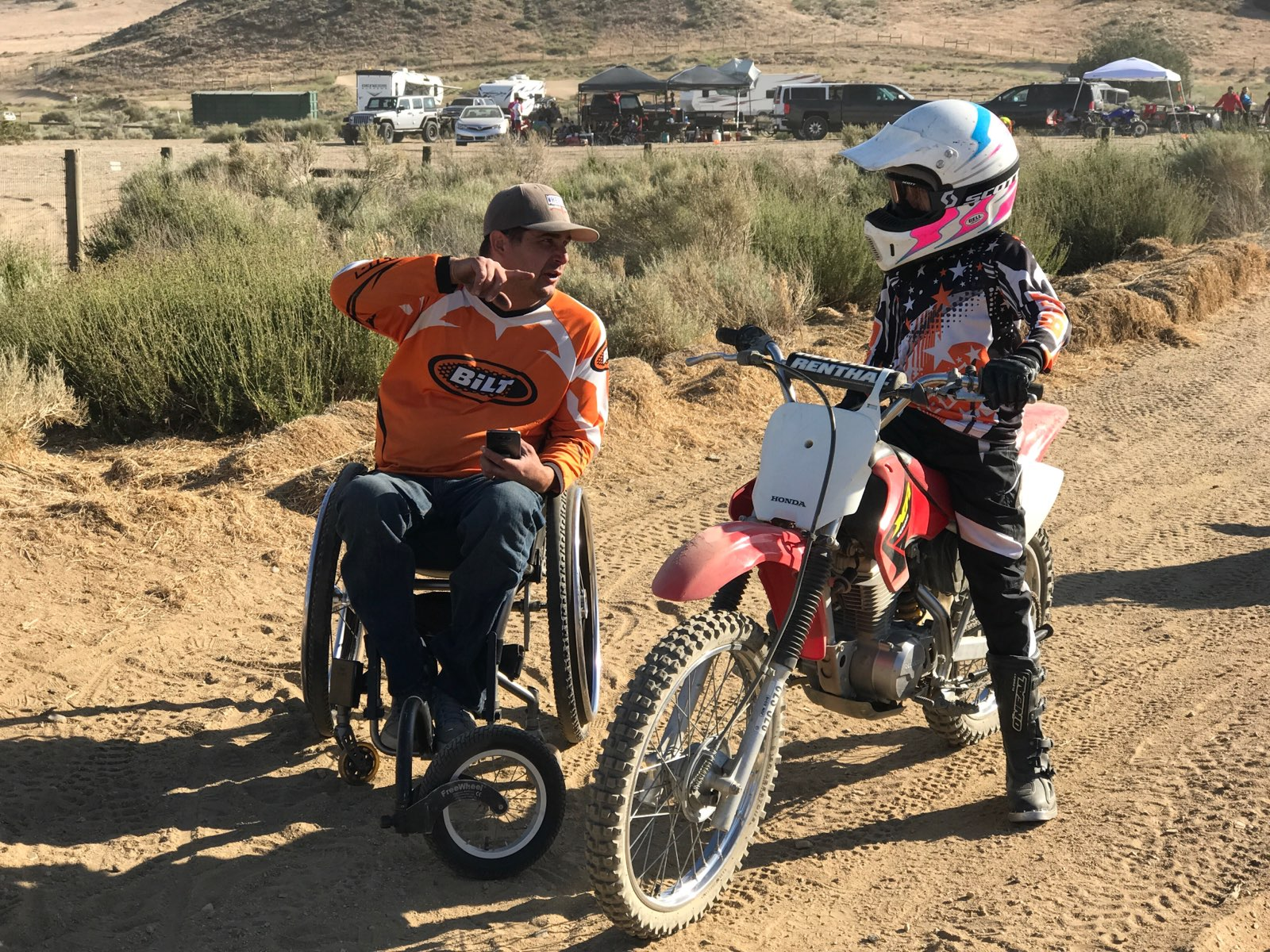 Anthony Orefice in his wheelchair talks to a boy on a dirt bike.