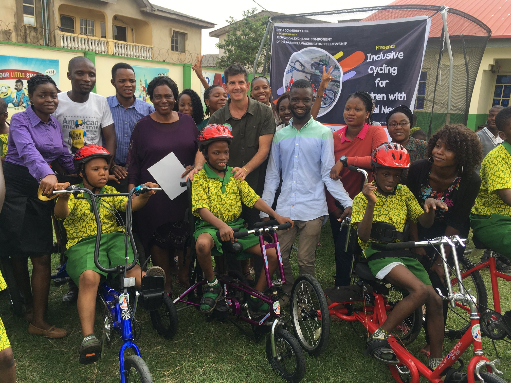 A group of adults stand behind three children on adaptive bicycles. An Inclusive Cycling banner is behind them.