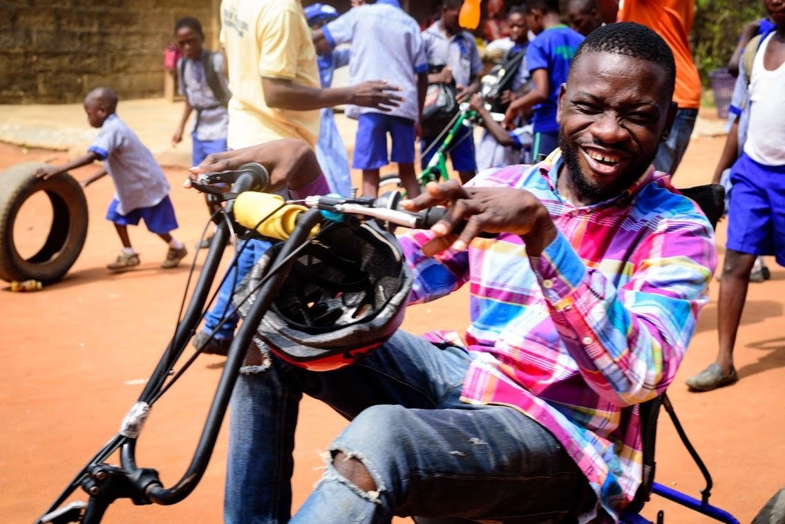 A young Nigerian man smiles big while sitting on an adaptive bike.