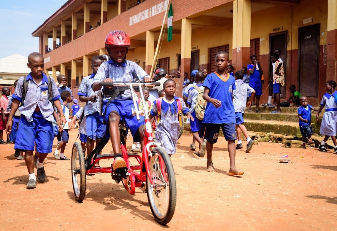 A young Nigerian boy pedals an adaptive bike while his classmates walk alongside him.