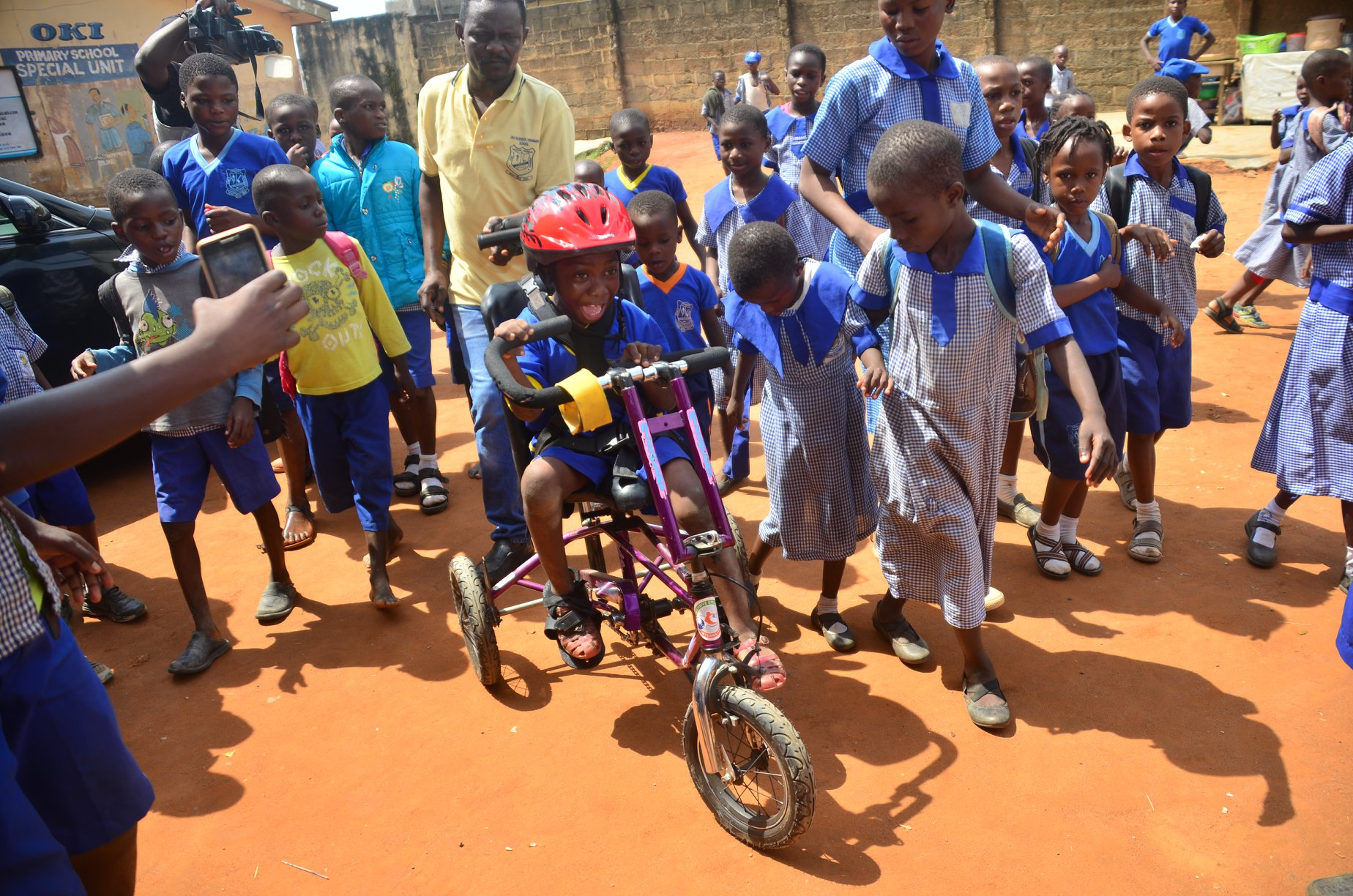 A young Nigerian boy smiles with awe as he pedals an adaptive bike. His classmates and some adults surround him.
