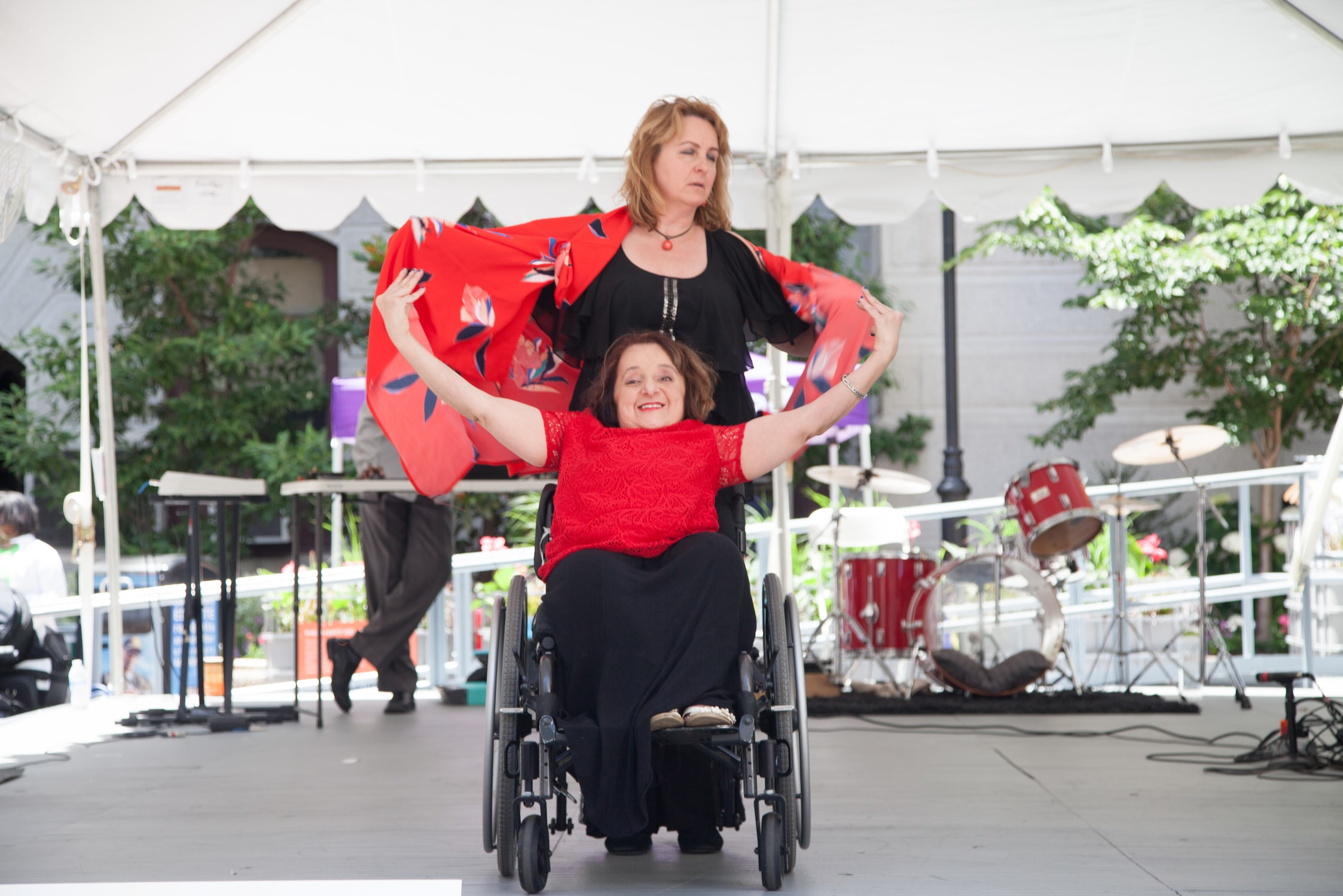 Two women wearing red and black on a stage. One woman is in a wheelchair holding her arms out wide while the other woman does the same while standing behind her.
