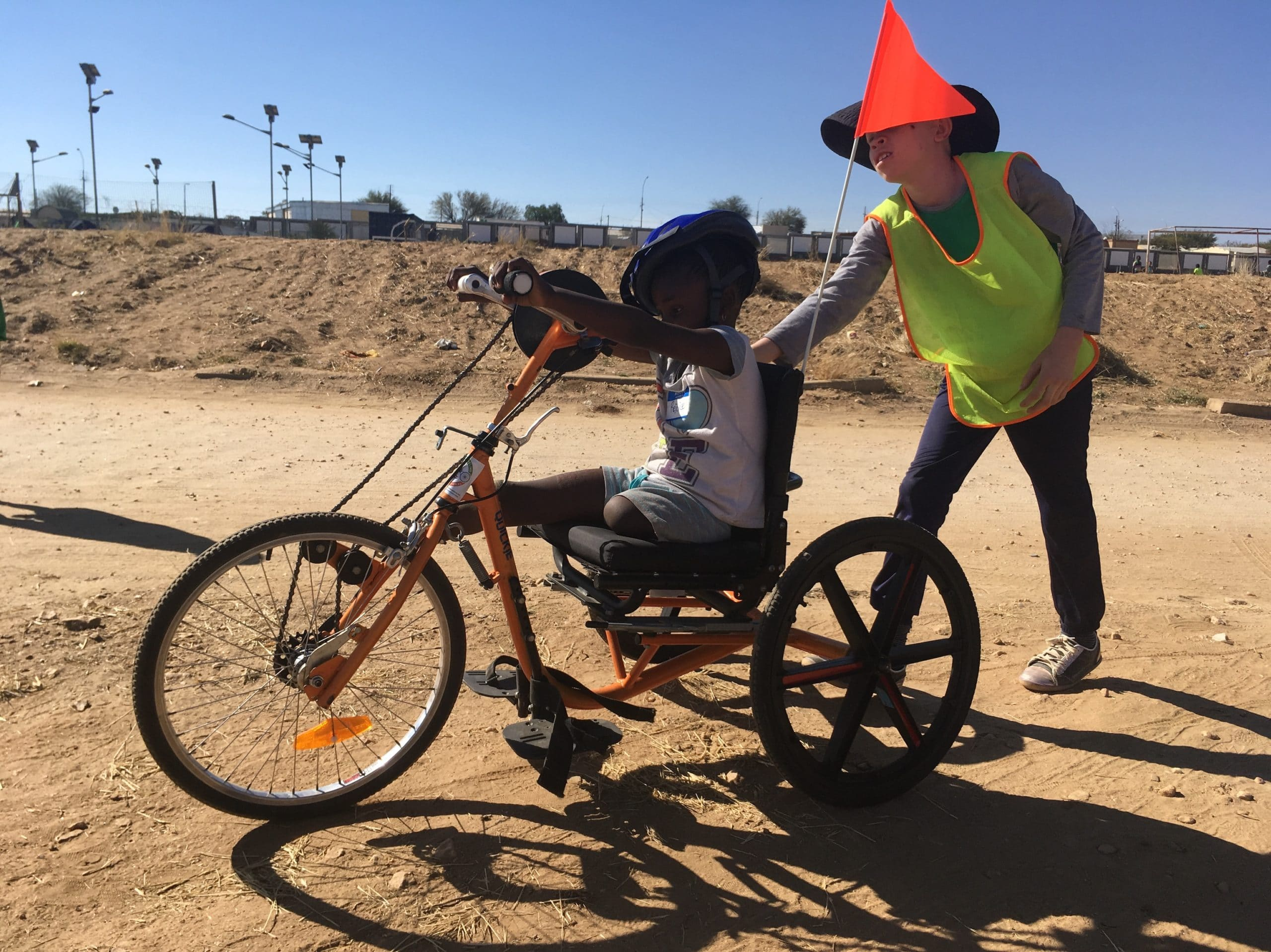 A leg-amputee child sits on an adaptive bike while another child stands behind with one hand on the bike as if he's pushing it.