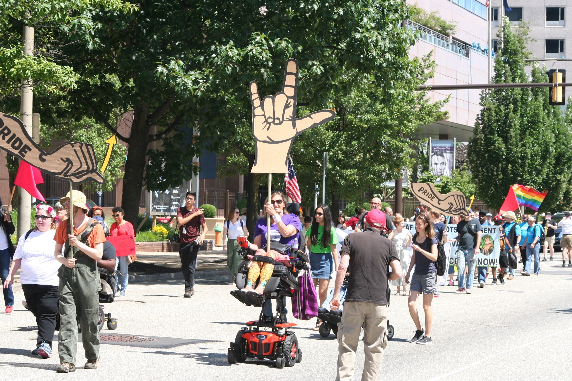 """A woman in a power wheelchair holds a sign showing """"I love you"""" in American Sign Language. Many people are marching and rolling behind her holding various signs."""