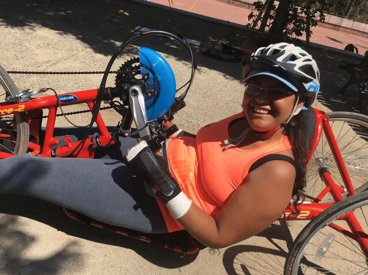 A young woman on a recumbent handcycle. She is smiling at the camera.