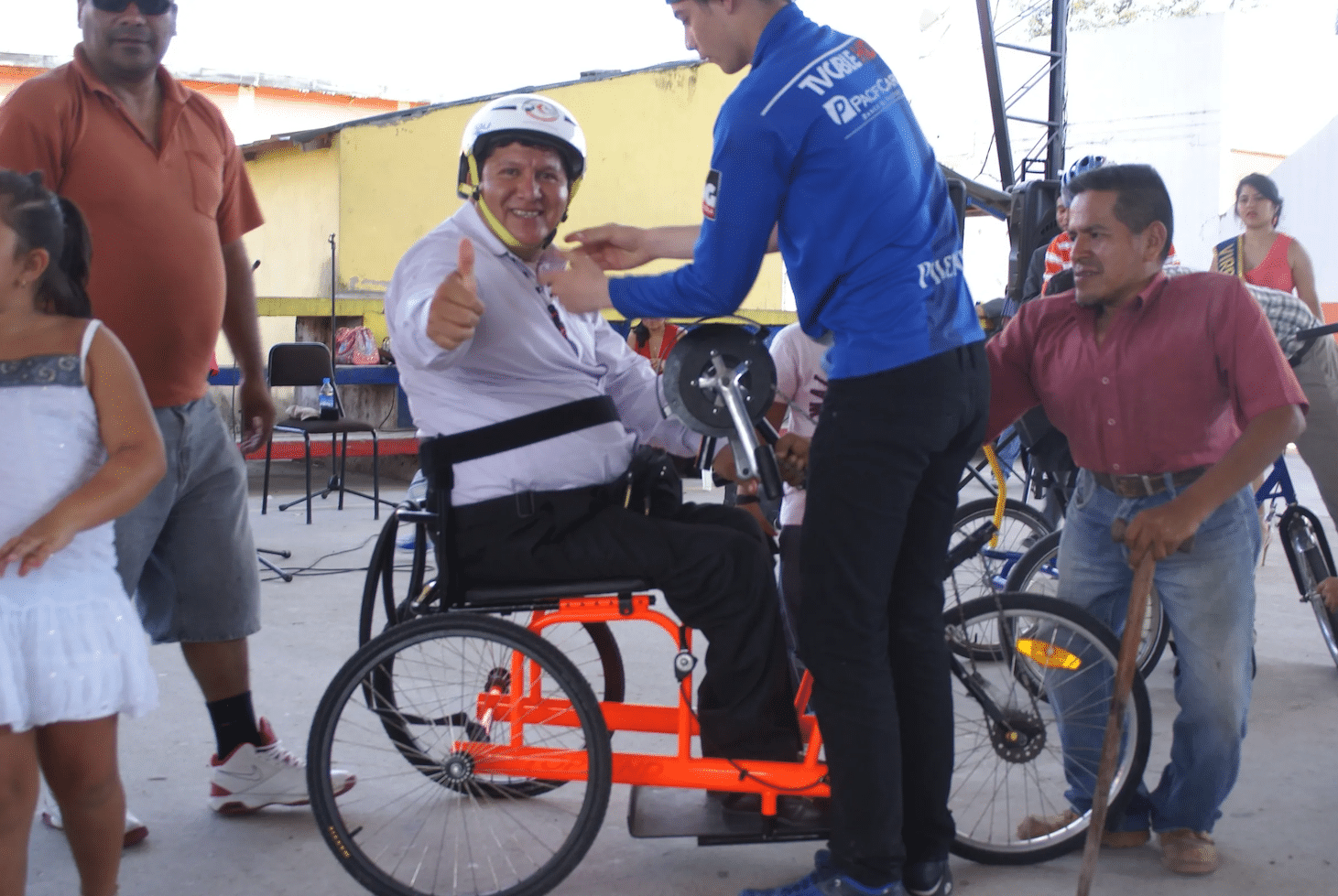 A man sits on an adaptive bike while an assistant straps him in. He's looking at the camera holding his thumb up.