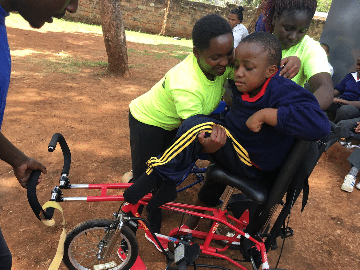 A young African boy lifts another young African boy onto a red adaptive bike.