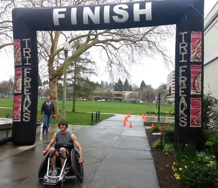 Jayden passing through the finish line in his racing wheelchair at the Tri Freaks race.