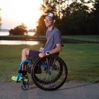 A side view of Jayden sitting in his wheelchair smiling at the camera. There is a grassy lawn and a lake in the background. The sun is setting.