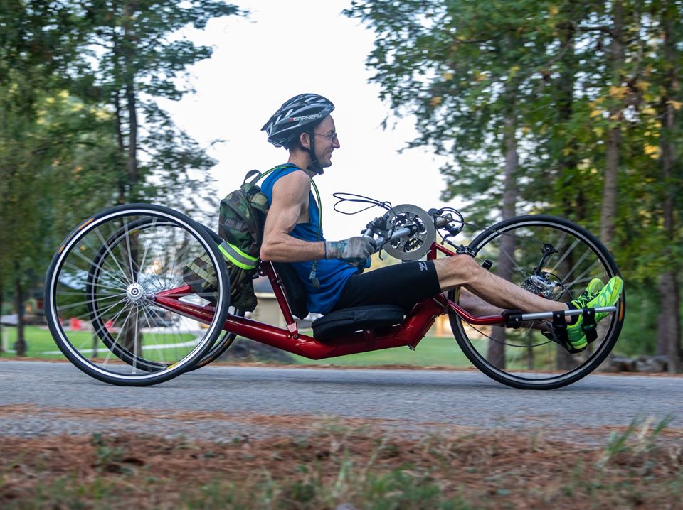 A side view of Jayden smiling while riding his handcycle on a cement path outside with trees all around..