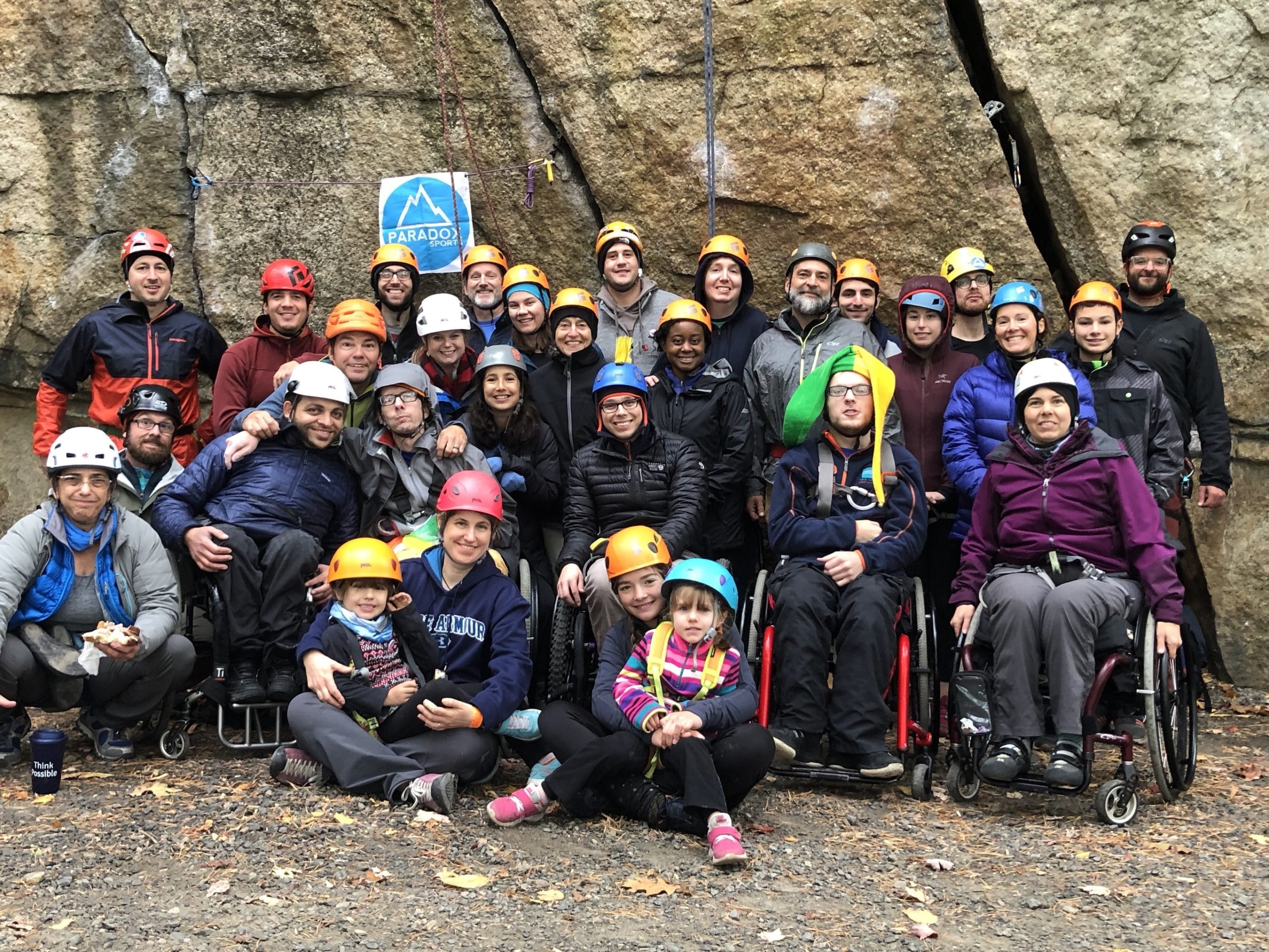 A group of climbers with and without disabilities wearing safety helmets in front of a cliff smiling at the camera.