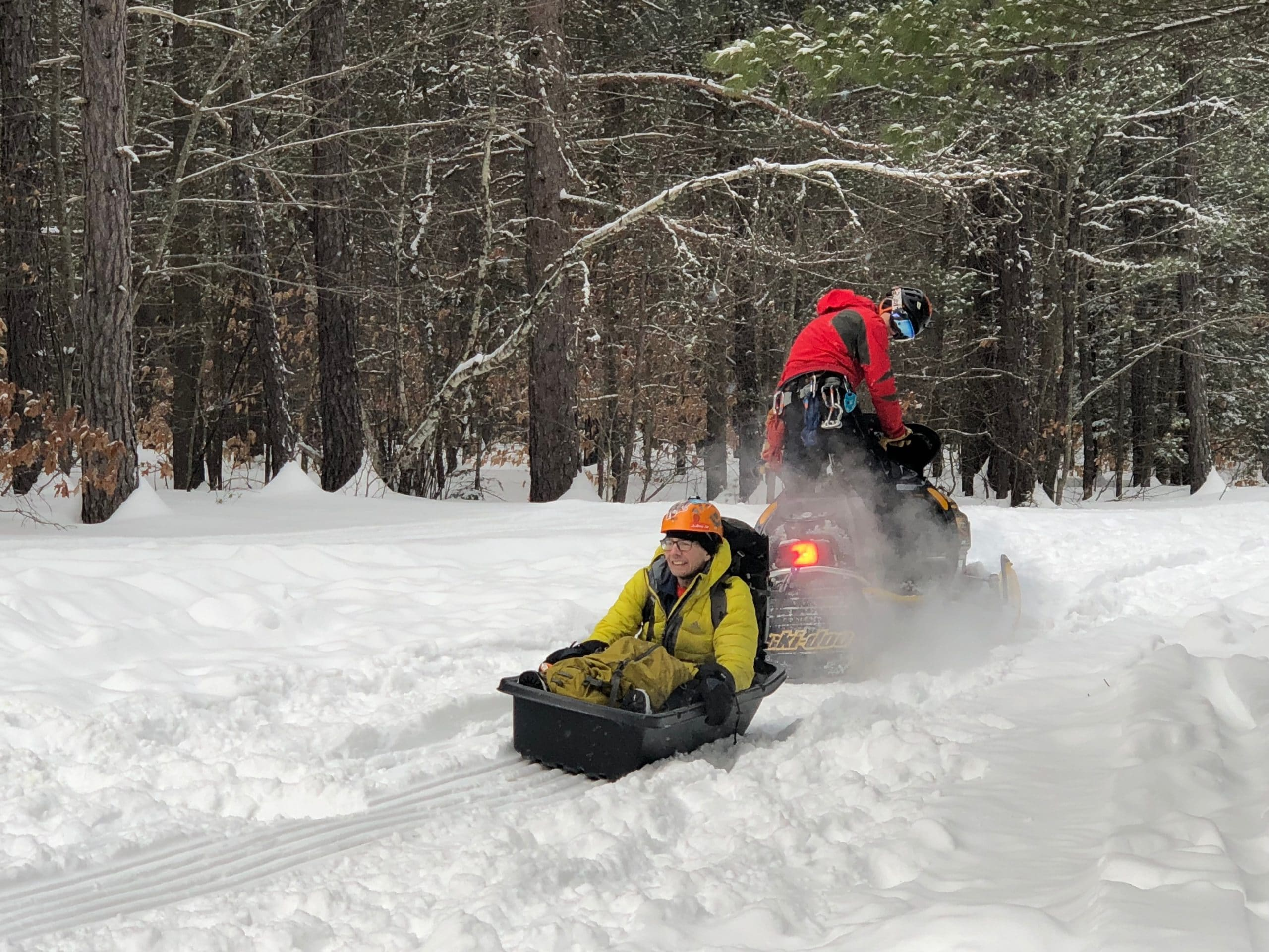A snowmobile pulls a sled holding a man in a yellow snowsuit and orange helmet.