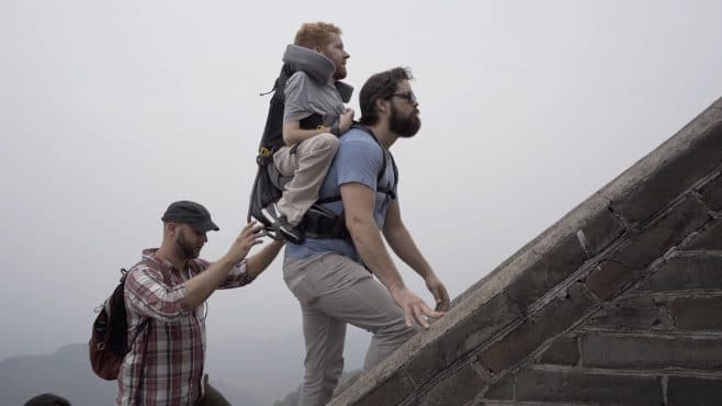 Three men on an outdoor stone staircase. One of them is carrying another in a backpack. The third is spotting from behind.