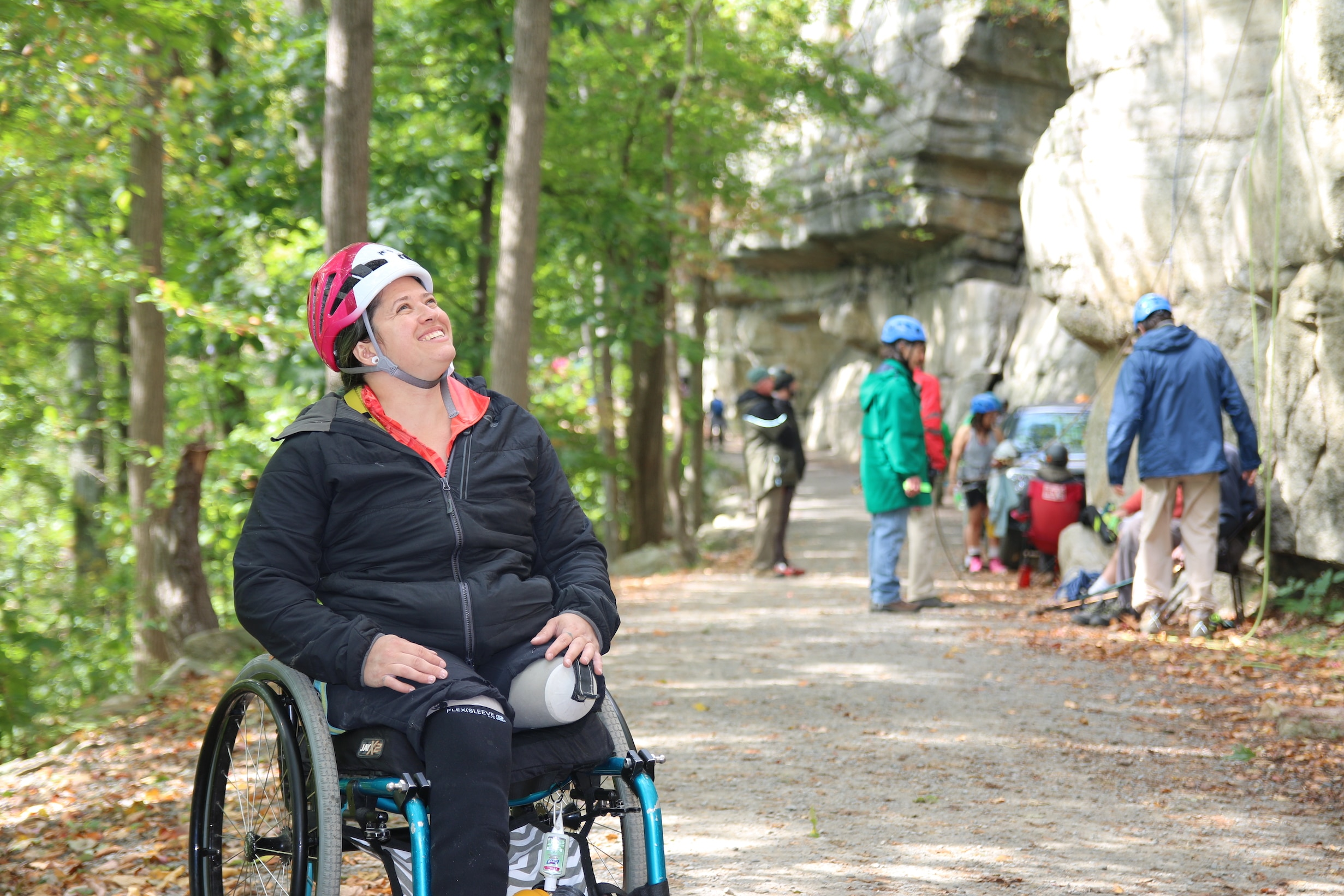 A woman single-leg amputee in a wheelchair wearing a helmet looks up toward the mountain and smiles. In the background, people prepare their climbing equipment.