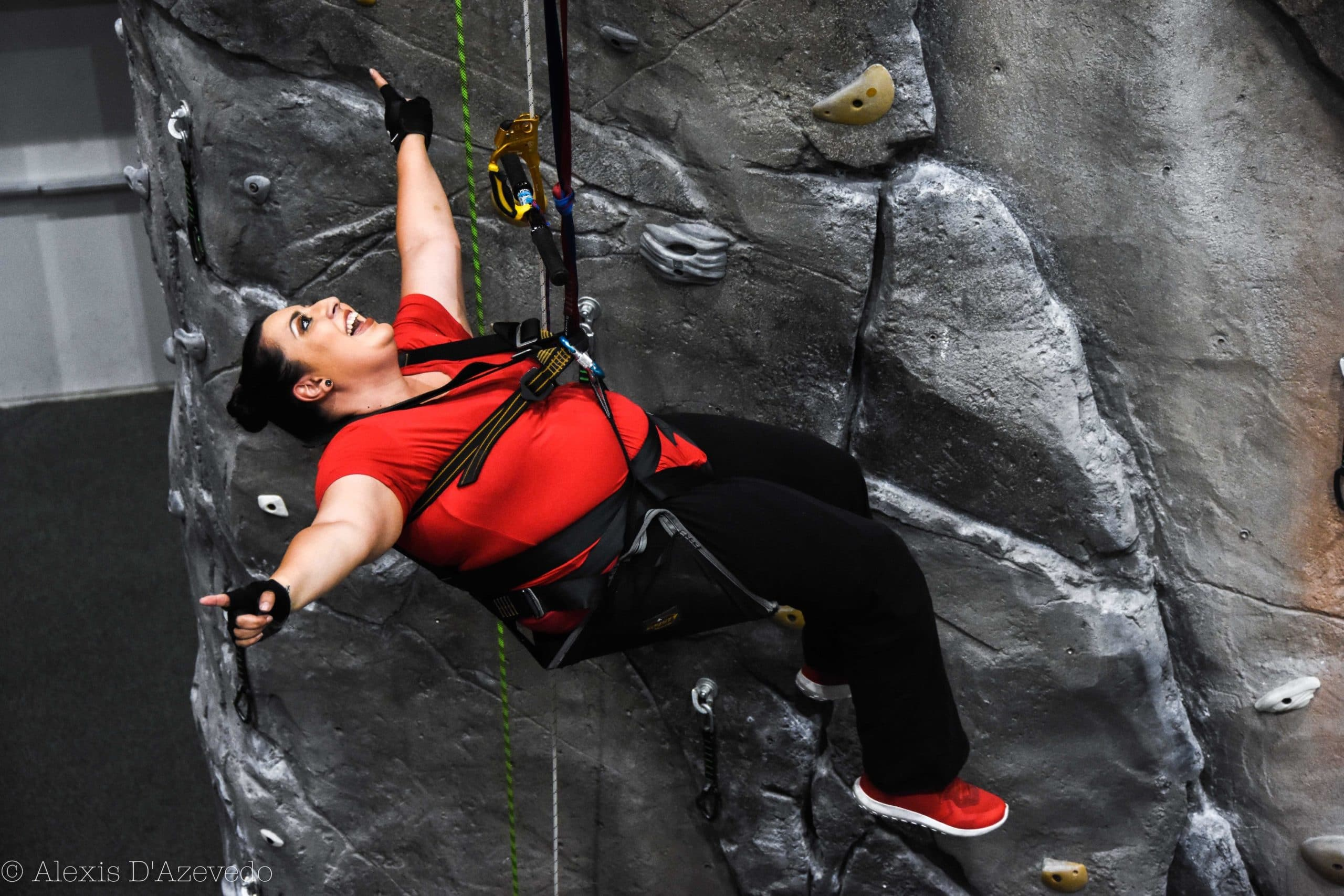 A woman outstretches her arms and leans back in her climbing chair as if to celebrate making it up the indoor wall.