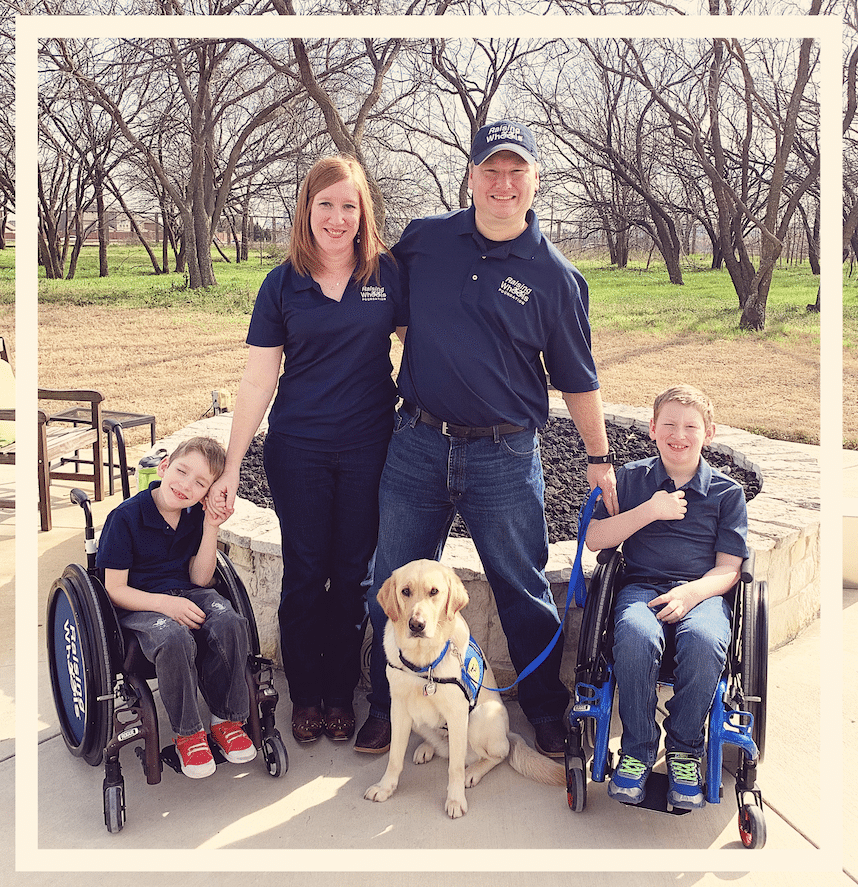 Two boys in wheelchairs with their mother, father, and dog standing between them.