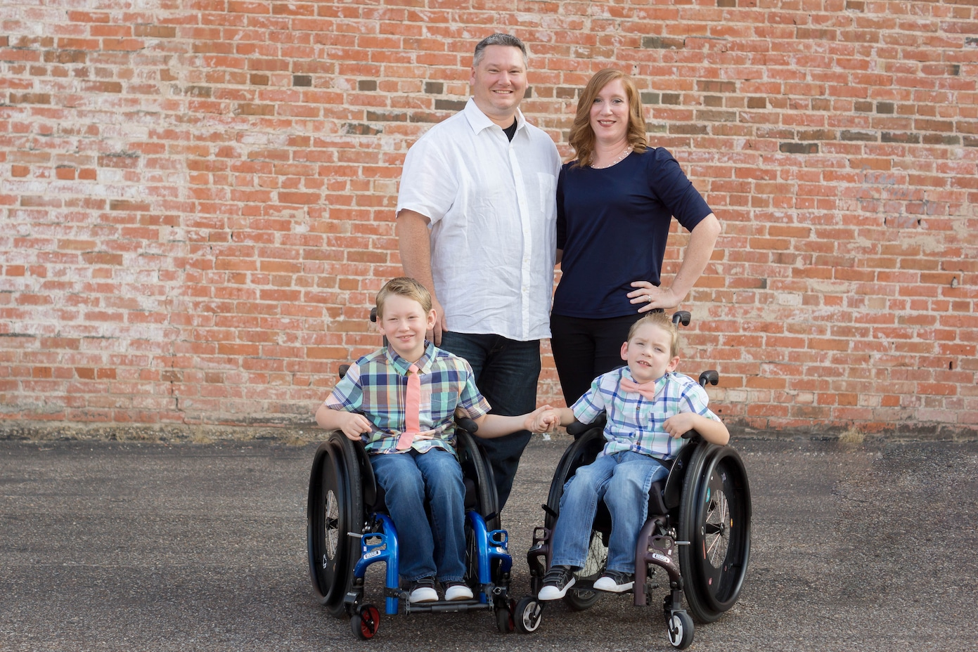 The Copp Family, Jody, Melissa, Calan, and Lawson in front of a brick building smiling at the camera.