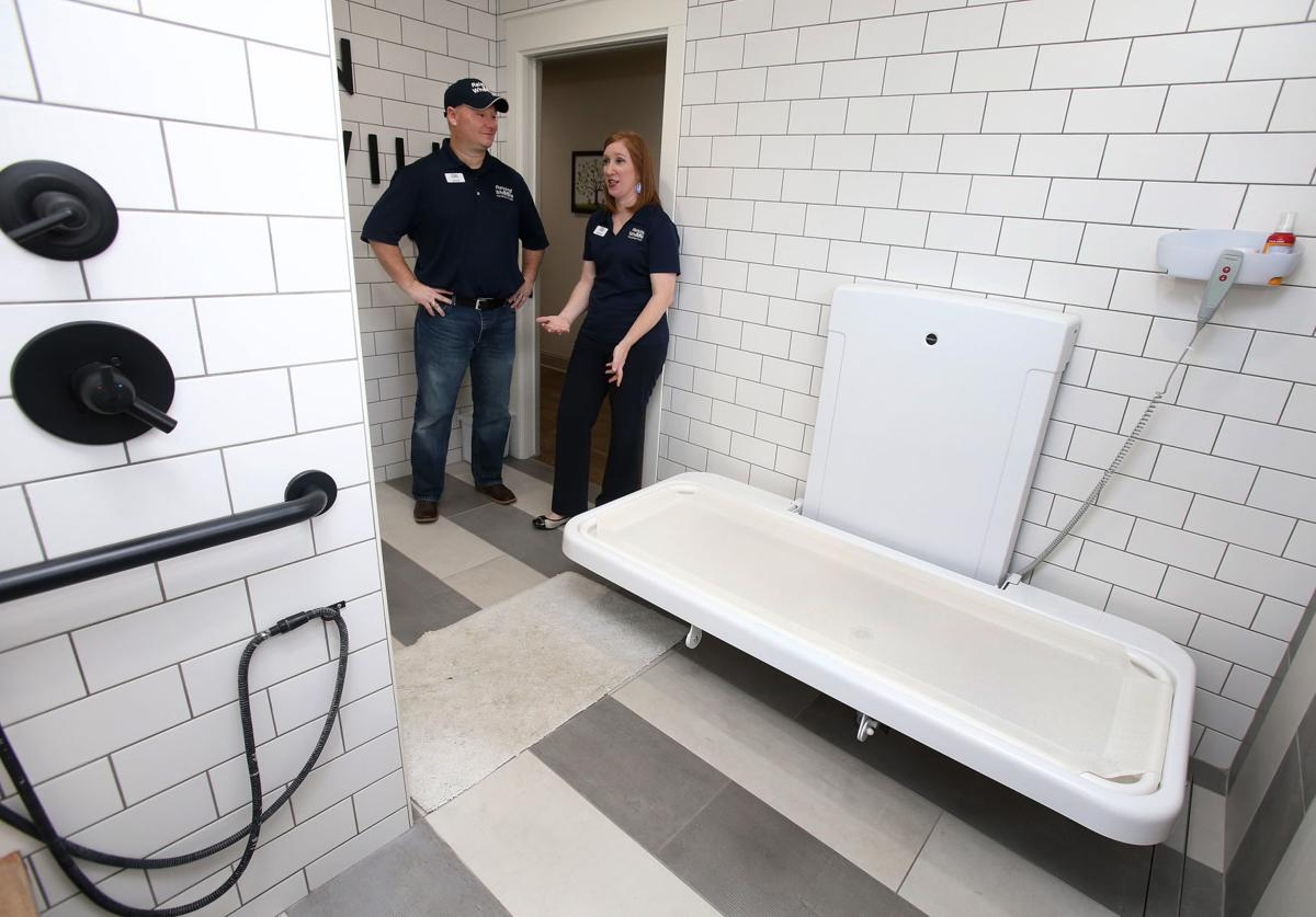 A white, tiled bathroom with a changing table. Jody and Melissa Copp are standing in the doorway.
