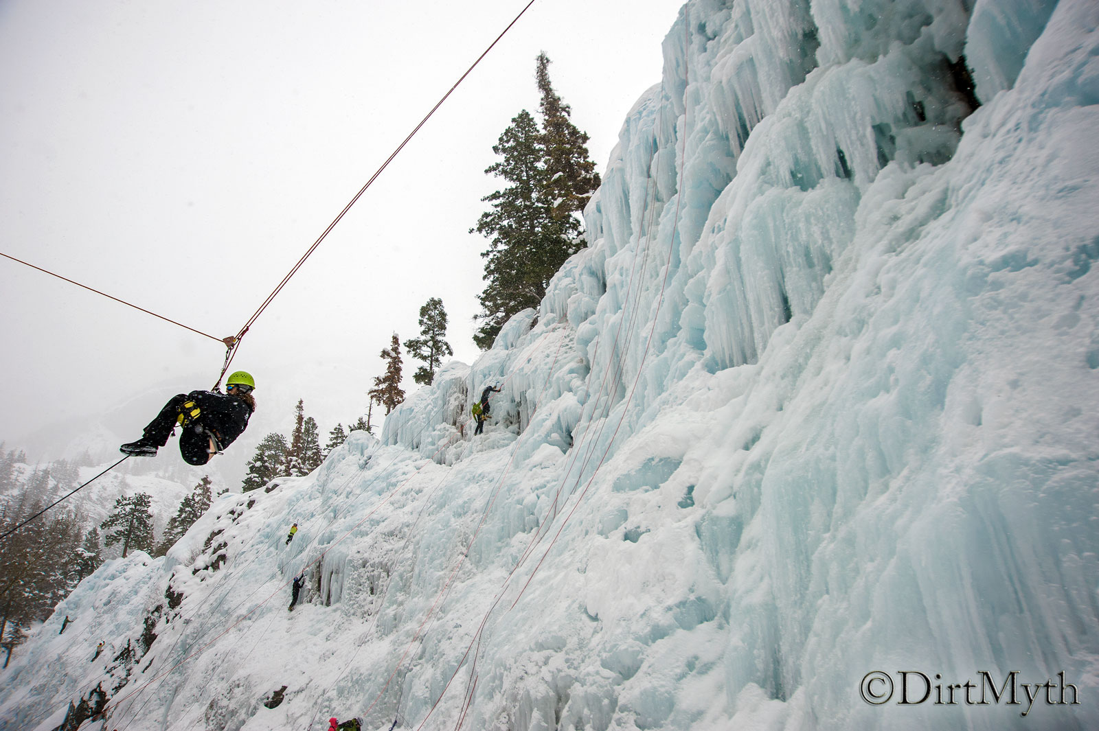 A person zips down an icy mountain with the help of a rope and pulley system.
