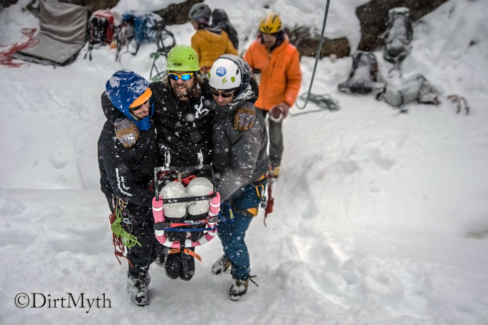 Two men carry another man up a snowy hill.