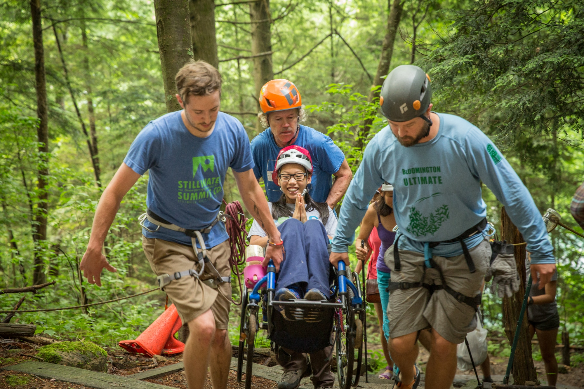 Three men wearing climbing equipment carry a smiling girl in her wheelchair up a set of wooden stairs in the forest.