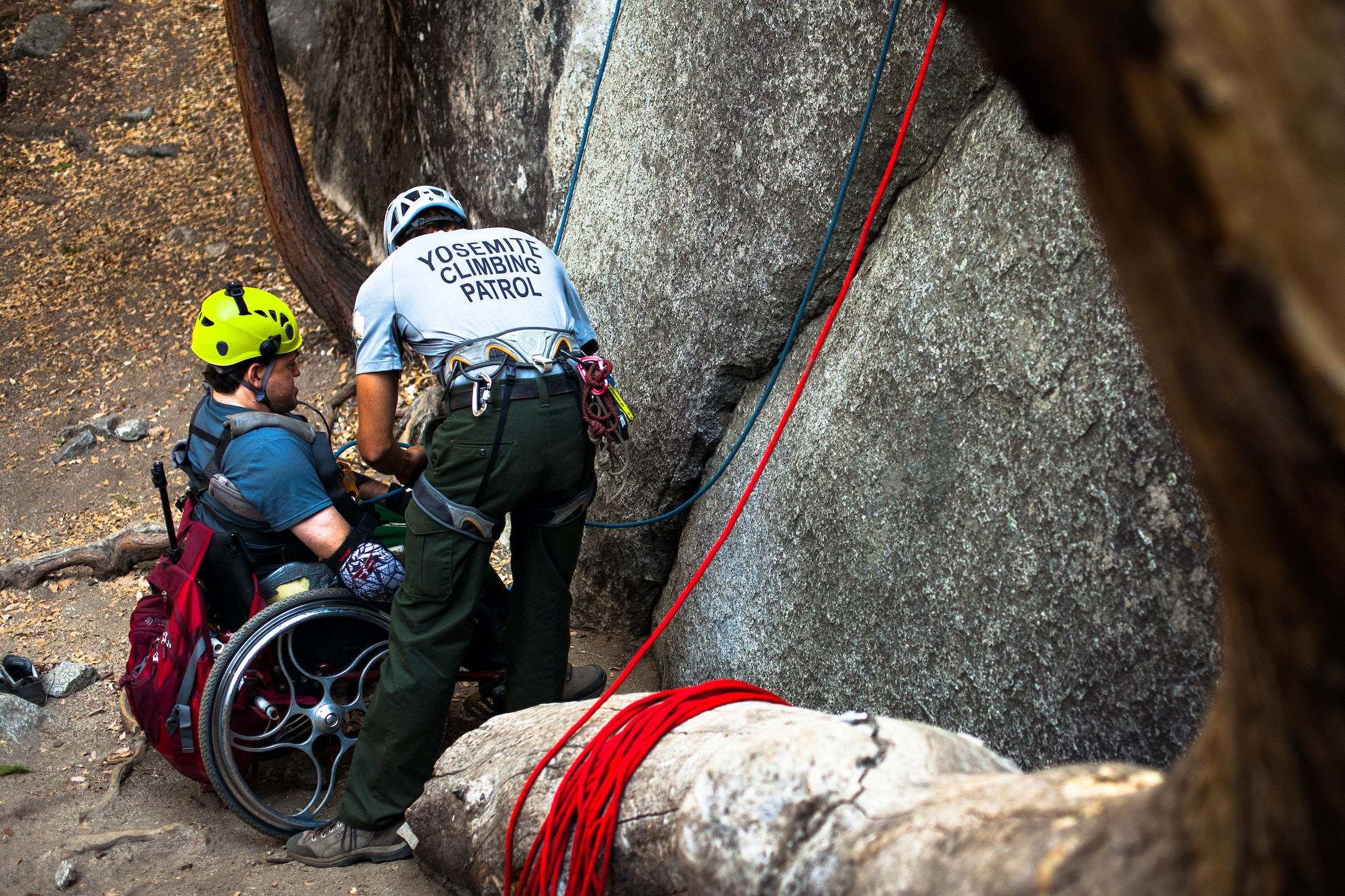 """A man wearing a """"Yosemite Climbing Patrol"""" t-shirt helps a man in a wheelchair prepare to climb the cliff in front of them."""